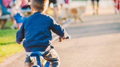 Malý kluk jede na dětském kole