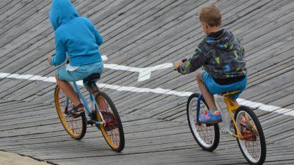 Chlapci jezdí po oválu na dětských kolech