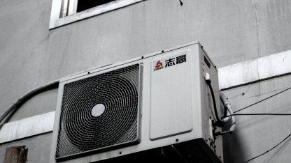 Venkovní jednotka klimatizace na fasádě domu.