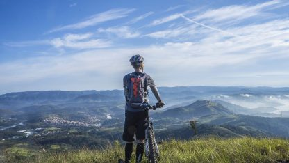 Muž na horském kole na vrcholu kopce