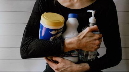 Žena držící více čisticích prostředků